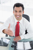 Businessman offering a handshake at office desk — Stock Photo
