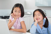 Two smiling young girls with laptop in kitchen — Stock Photo