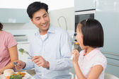Father watching little girl eat food with a fork in kitchen — Foto de Stock