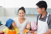Happy family of four smiling in kitchen — Stock Photo