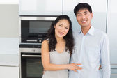 Portrait of a smiling young couple in the kitchen — Stock Photo