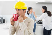 Architect in hard hat drinking coffee with family in background — Stockfoto