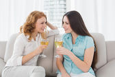 Young female friends with wine glasses at home — Stock Photo