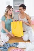 Smiling women sitting on floor with shopping bag — Stockfoto