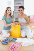 Smiling women sitting on floor with shopping bag — Stock Photo