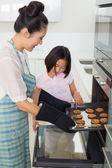 Girl helping her mother prepare cookies in kitchen — Stockfoto