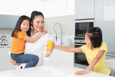 Girl offering her mother a glass of orange juice in kitchen — Stock Photo