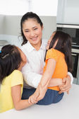 Smiling mother with her young daughters in kitchen — Stock Photo