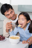 Father with young daughter having cereals in kitchen — Stockfoto