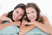 Two smiling young female friends lying in bed — Stock Photo