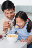 Father with young daughter having cereals in kitchen — Stock Photo