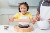 Shocked girl with her father preparing cookies in kitchen — Stockfoto