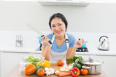Smiling woman chopping vegetables in kitchen — Stock Photo