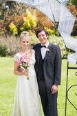 Attractive newlyweds smiling at camera — Stock Photo