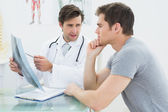 Male doctor explaining spine x-ray to patient — Stock Photo