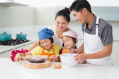 Happy family of four preparing cookies in kitchen — Stock Photo