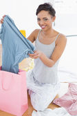 Smiling woman sitting on floor with new dress and shopping bag — Stockfoto