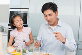 Little girl watching father eat food with a fork in kitchen — Stock Photo