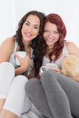 ベッドの中でコーヒー カップと幸せな若い女性の友人 — ストック写真