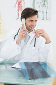 Souriant jeune homme médecin à l'aide de téléphone — Photo