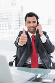 Businessman gesturing thumbs up while on call at office desk — Stock Photo