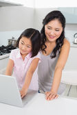 Smiling mother with young daughter using laptop in kitchen — Stock Photo