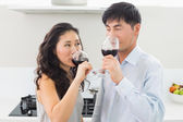 Loving young couple drinking red wine in kitchen — Stock Photo