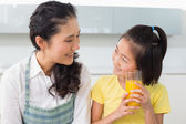 Young girl holding orange juice with her mother in kitchen — Stock Photo