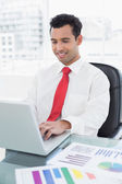 Smiling young businessman with laptop and graphs — Stockfoto