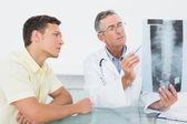 Doktor vysvětlení rtg plic pacienta v úřadu — Stockfoto
