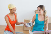 Happy friends unwrapping boxes in a new house — Stock Photo