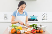 Woman chopping vegetables in kitchen — Stock Photo