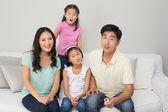 Portret van een familie van vier kijken tv in de woonkamer — Stockfoto