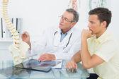 Läkaren förklarar ryggraden patienten i office — Stockfoto