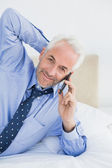 Mature businessman using mobile phone in bed — Stock Photo