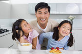 Smiling man with happy two daughters having breakfast in kitchen — Stock Photo