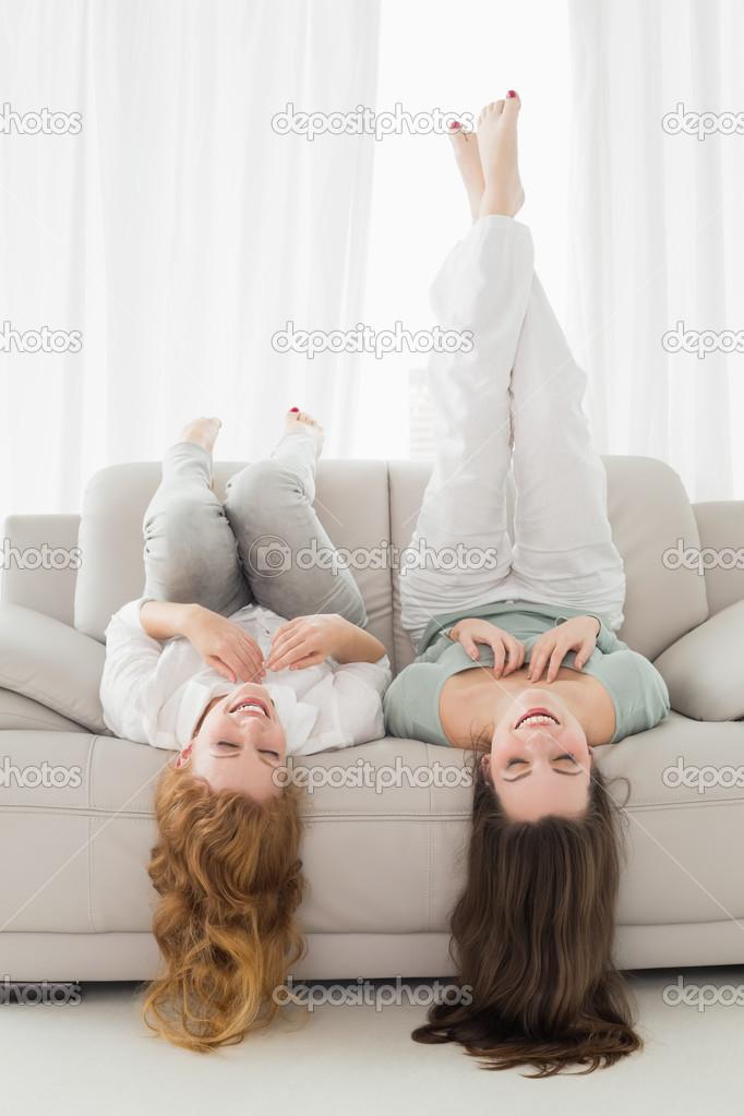freundinnen auf sofa im wohnzimmer liegen — stockfoto