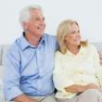 Senior couple sitting on sofa while looking away — Stock Photo #38986507