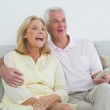 Cheerful senior couple with remote control at home — Stock Photo