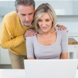 Couple looking at laptop in kitchen — Stock Photo