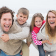 Couple piggybacking kids at the beach — Stock Photo