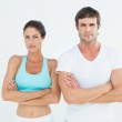Portrait of a fit young couple with arms crossed — Stock Photo #38981767