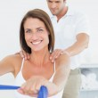Male therapist assisting young woman with exercises — Stock Photo #38982499