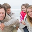 Happy couple piggybacking kids at beach — Stock Photo