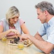 Couple playing chess at home — Stock Photo