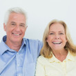 Cheerful loving senior couple sitting on sofa — Stock Photo