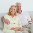 Relaxed happy senior couple with remote control at home — Stock Photo