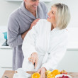 Man with a woman as she cuts fruits in kitchen — Stock Photo