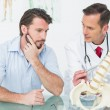 Stock Photo: Male doctor explaining spine to patient