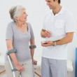 Therapist discussing reports with a disabled senior patient — Stock Photo